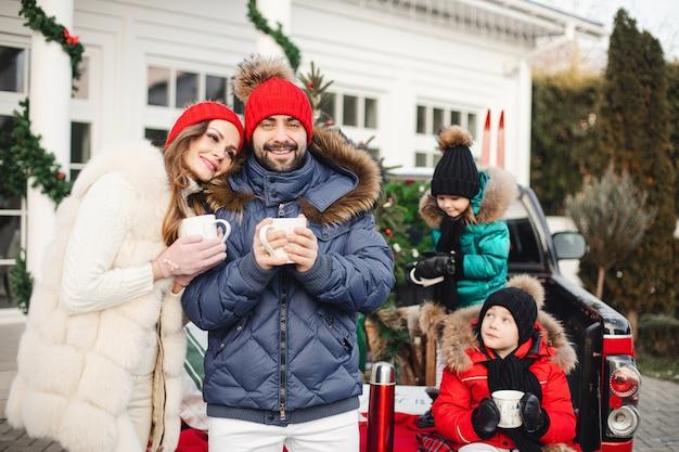 새해 선물과 크리스마스 트리를 가진 부모와 자녀 아빠 엄마 딸과 아들이 차로 크리스마스 휴가를 가고 있습니다