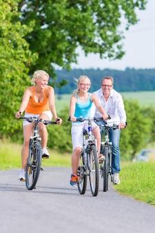 Родители и дочь отправляются в велопрогулку по проселочной дороге.
