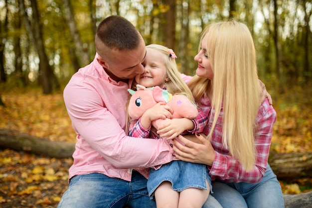 Родители и дочь обнимаются и сидят на бревне на фоне осеннего парка.