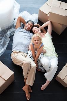 親と娘が床にたくさんの箱を置いています