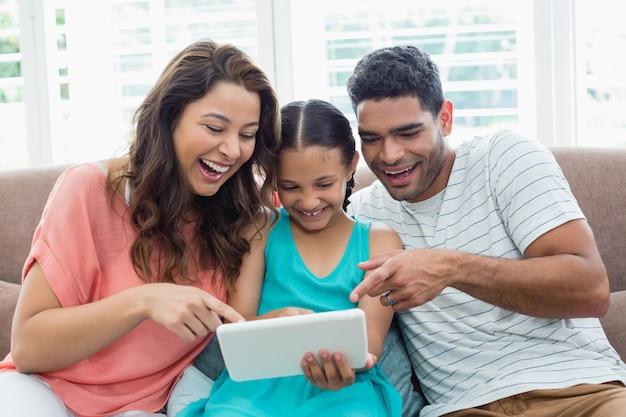 両親と娘のリビングルームでデジタルタブレットを使用して