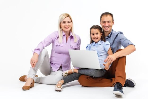 Родители и дочь, использующие ноутбук