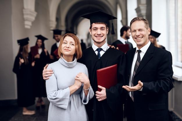 両親と卒業パーティーで一緒に写真を撮ります。