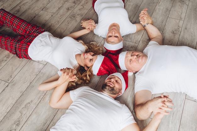 Родители, бабушки и дедушки вместе проводят время на рождество и отдыхают на полу.