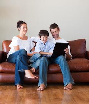 ソファーでラップトップで遊んでいる両親と子供