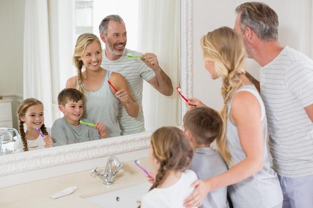 Родители и дети чистят зубы в ванной комнате