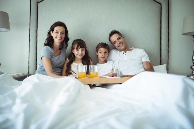 両親とベッドで朝食を持っている子供たち
