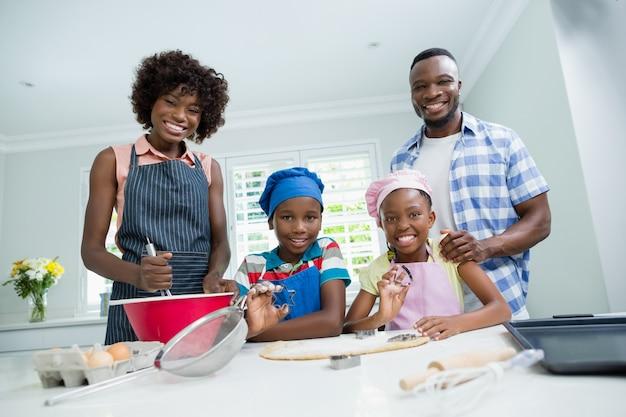 両親と子供たちが自宅のキッチンで食事の準備