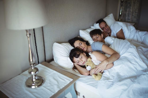 両親とベッドで寝ている子供たち