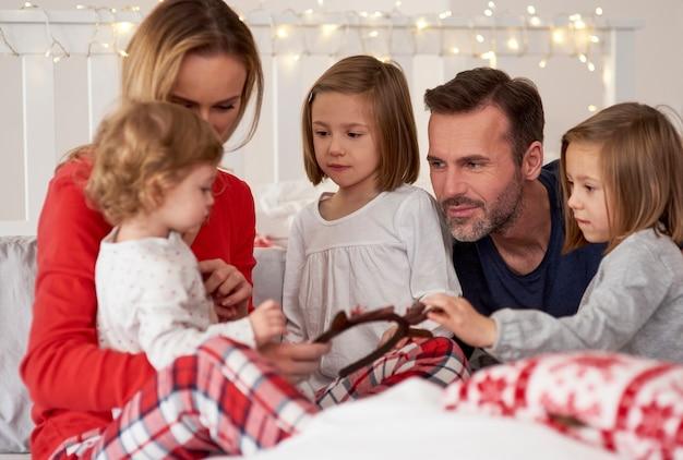 ベッドでクリスマスの朝を過ごす親子