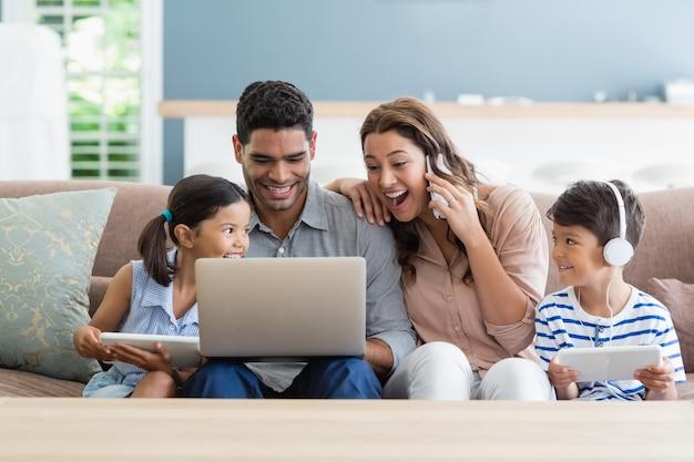 거실에서 랩톱 및 디지털 태블릿을 사용하는 부모와 아이들
