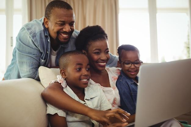 Родители и дети, используя ноутбук в гостиной
