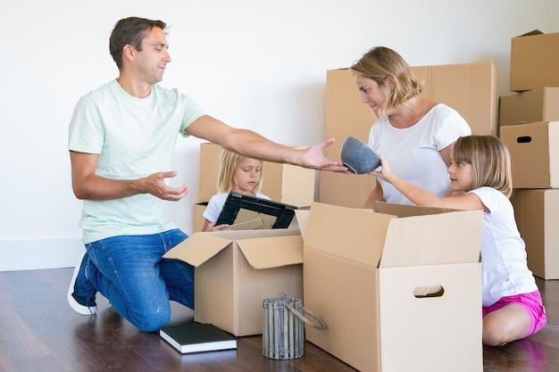 Родители и маленькие дочери распаковывают вещи в новой квартире, сидят на полу и вынимают предметы из открытых ящиков.