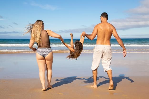 両親と小さな女の子が水着を着て、金色の砂の上を歩いて水に