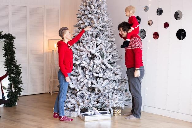 家でクリスマスツリーを飾る両親と幼い息子の男の子。メリークリスマス、そしてハッピーニューイヤー