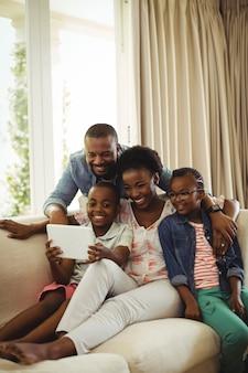 Родители и сын с помощью цифрового планшета на диване в гостиной