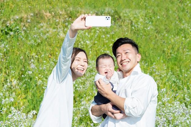 屋外で記念写真を撮る親と赤ちゃん