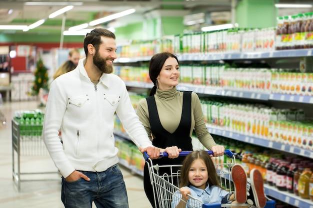 Родители и их милая маленькая дочь улыбаются, выбирая еду в супермаркете