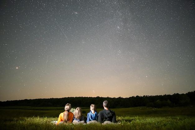 많은 밝은 별이 있는 어두운 하늘을 관찰하는 야간 들판에서 휴식을 취하는 부모와 자녀.