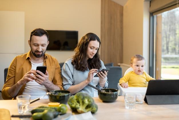 両親と自宅で昼食時にモバイルデバイスに座っている1歳の男の子
