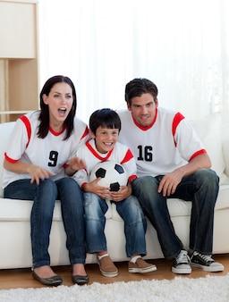 Родители и их сын смотрят футбольный матч