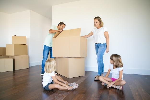 부모와 두 딸이 새 빈 아파트에서 상자를 열고 물건을 풀고 있습니다.