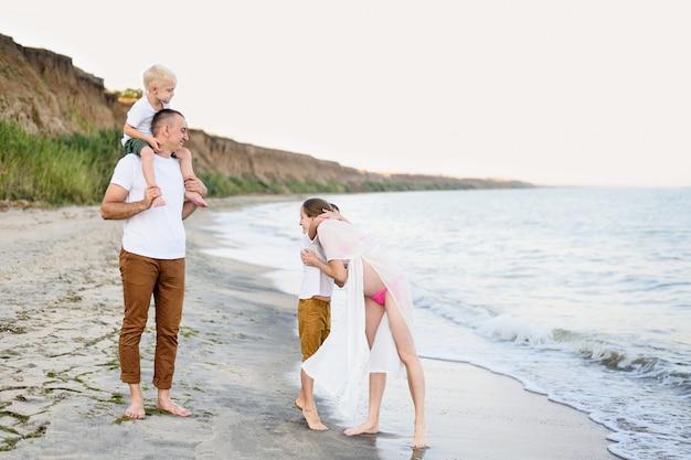 Родители и двое сыновей развлекаются на берегу моря