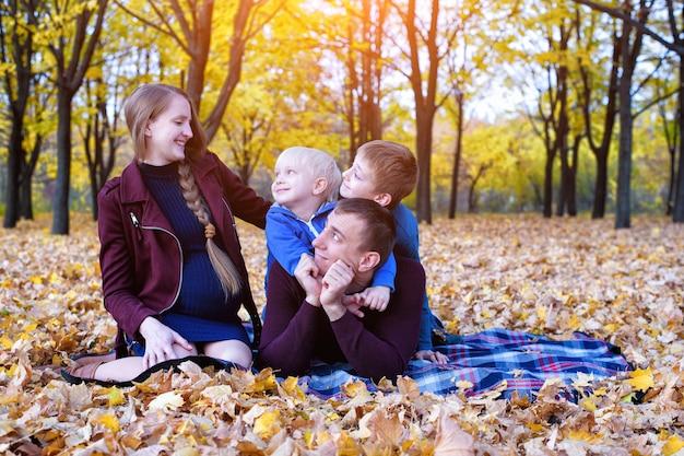両親と2人の息子が公園でリラックスしておしゃべりします。妊娠中のお母さん幸せな家族。黄色い紅葉、晴れた日
