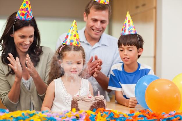 誕生日のケーキでろうそくを吹き飛ばした娘を拍手する親たち