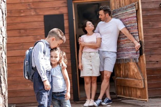 両親は2人の子供を学校に戻し、自宅で遠隔教育を楽しく終え、自宅の戸口に立っている子供たちに同行します。