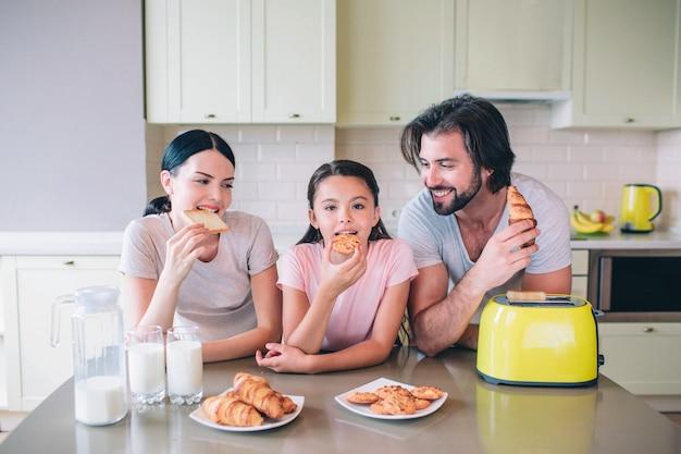 부모는 딸과 함께 테이블에 기대어 있습니다. 남자는 작은 여자를 찾고 있습니다. 그녀와 그녀의 어머니는 롤을 먹고있다. 테이블에는 우유, 크로아상 및 노란색 토스터가 있습니다.
