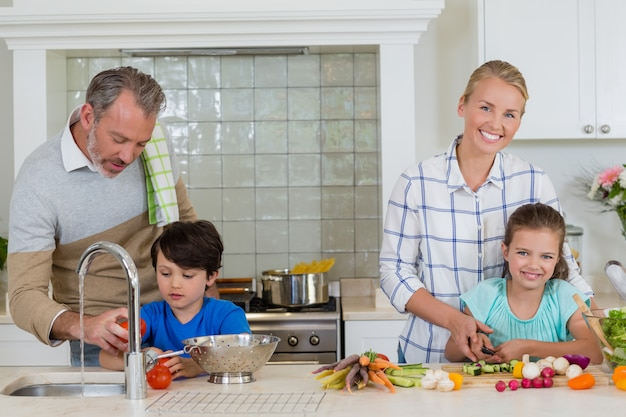 Parents assisting a kids to chop and clean the vegetables in kitchen