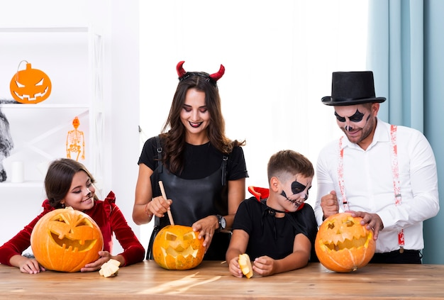 Parents carving pumpkins with children