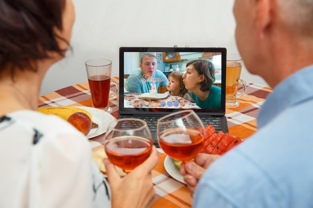 Parents celebrate the girl's birthday through a video call of a virtual party with grandparents.