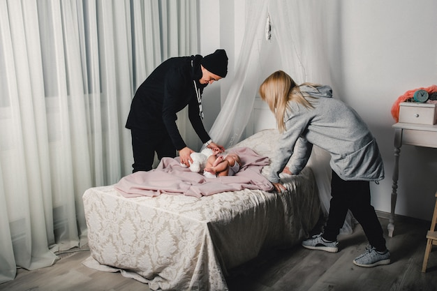 Parents change the little baby on the bed