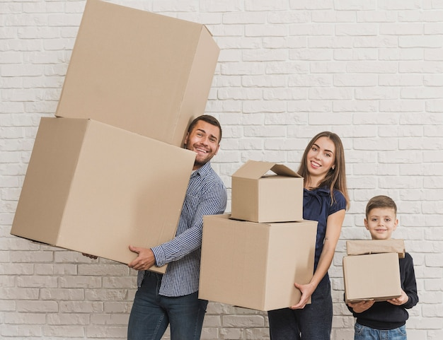 Parents and child holding cardboard boxes