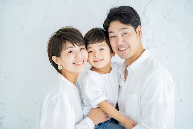 Parents and child lined up with a smile and a textured white background