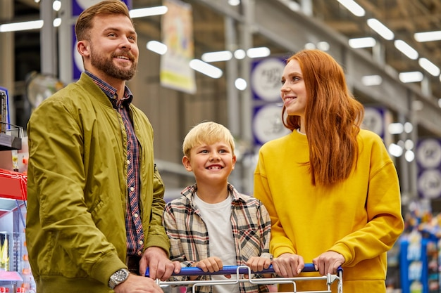Parents and child in supermarket, caucasian married couple buy fresh food in grocery store.family in shop