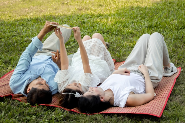 Parents and children are playing the tablet on the mat in the park.