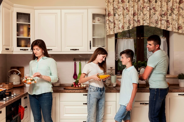 Parents and children preparing food in the kitchen together