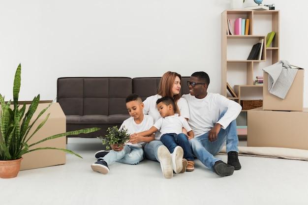 Genitori e figli stanno insieme sul pavimento di casa