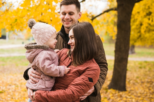Parents and daughter embracing in autumn park smiling
