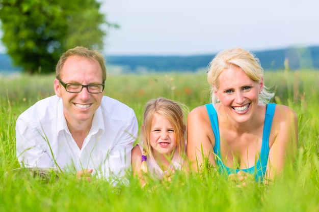 Parents and daughter laying on grass of lawn or field