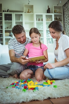 Parents and daughter reading a book while playing with building blocks