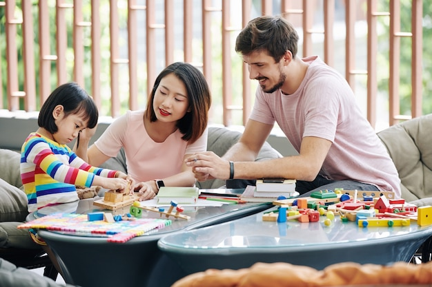 Parents and daughter solving toy puzzle