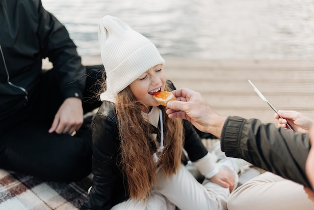 Parents feed their little daughter in a white hat with a sandwich happy family