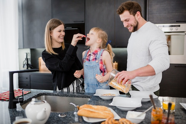 Parents feeding daughter in kitchen Free Photo