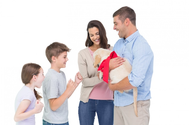 Parents gifting puppy to children against white background