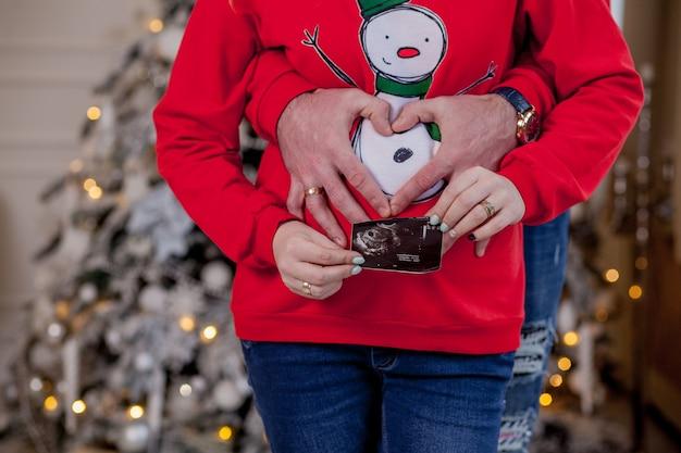 Руки родителей держат ультразвуковое сканирование, касаясь живота беременной возле елки