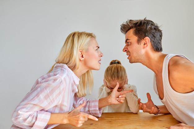 親は子供の女の子の前で喧嘩をしている、娘は母と父の喧嘩に苦しんでいる、悪い家族関係、別れ